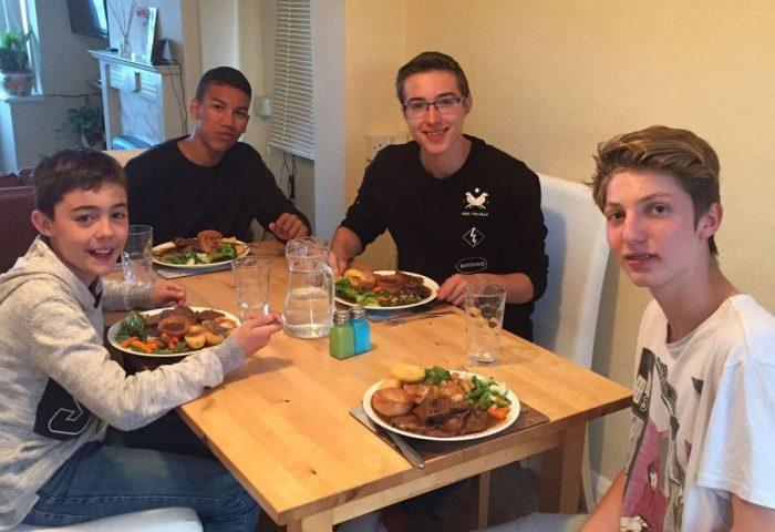 Studenti in una scuola estiva di studenti di lingua inglese che consumano la cena inglese arrosto